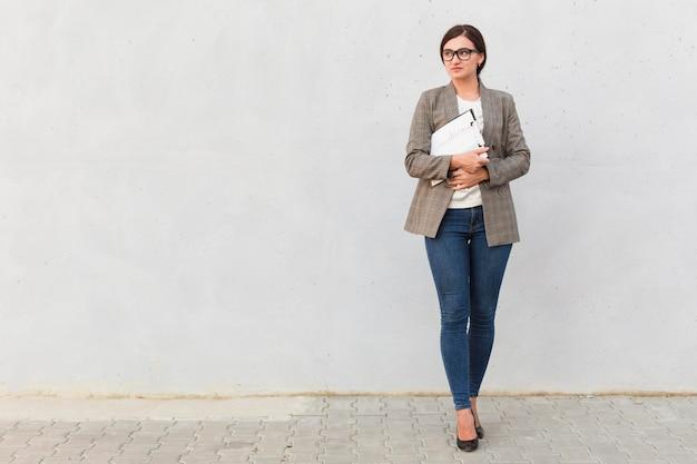 Вид спереди деловой женщины, позирующей с блокнотом на открытом воздухе