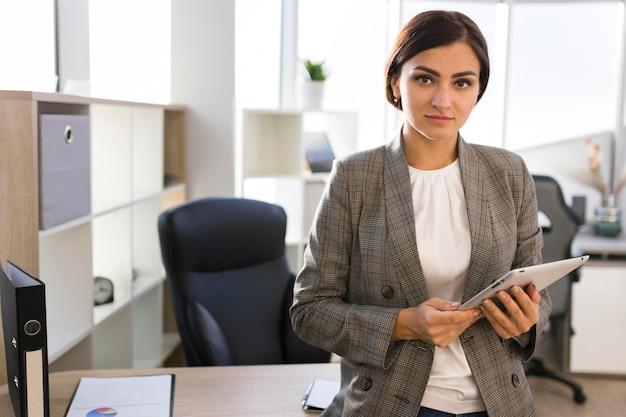 Деловая женщина позирует с планшетом в офисе, вид спереди