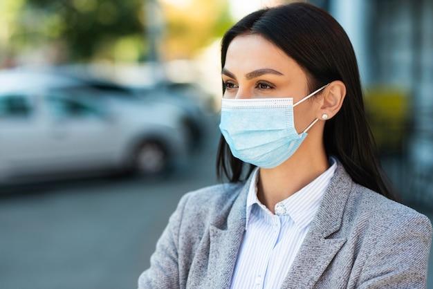 Вид спереди деловой женщины с медицинской маской и копией пространства