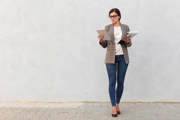 Вид спереди бизнес-леди с блокнотом и планшетом на открытом воздухе