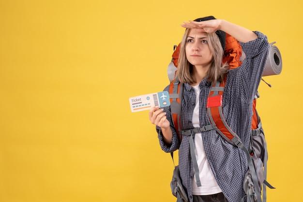 チケットを観察しているバックパックを持つ忙しい旅行者女性の正面図