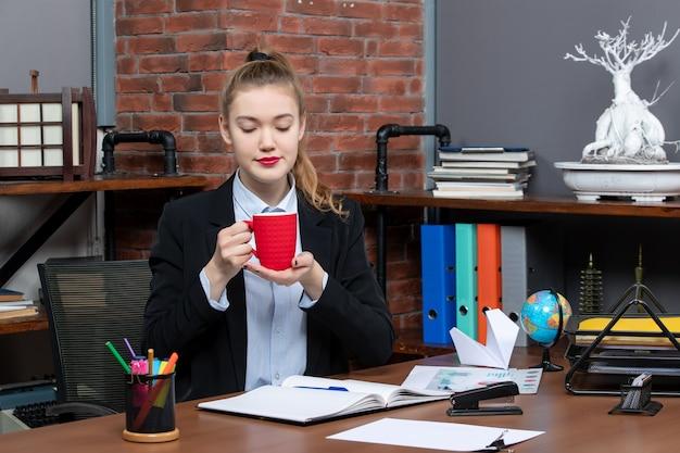 テーブルに座って、オフィスで赤いカップを保持している忙しい若い女性の正面図