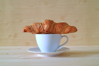 Front View of Butter Croissant with a Cup of Coffee on the Wooden Table