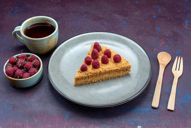 Вид спереди на кусочек торта вкусный с малиной и чаем на темной поверхности