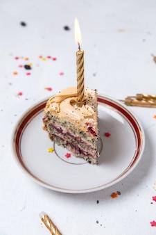 밝은 표면에 촛불 접시 안에 케이크 조각의 전면 모습