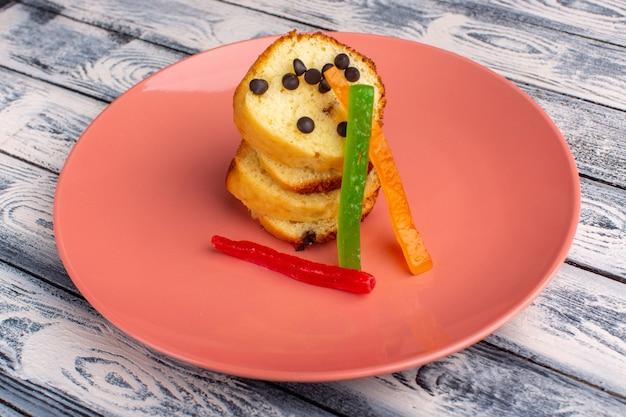 Вид спереди ломтиков торта внутри коричневой тарелки с шоколадными чипсами и мармеладом на светлом столе