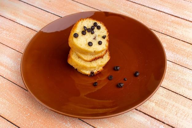 Вид спереди ломтиков торта внутри коричневой тарелки с шоколадными чипсами на светлом столе