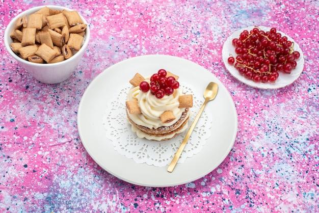 色付きの机の上のクランベリーとクラッカーと一緒にクリームとケーキの正面図