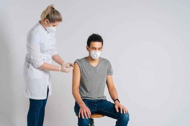 Вид спереди кавказского мужчины в лицевой маске, получающего вакцину против коронавируса на изолированном фоне. портрет врача с помощью шприца для введения вакцины пациенту для предотвращения распространения вируса covid19.