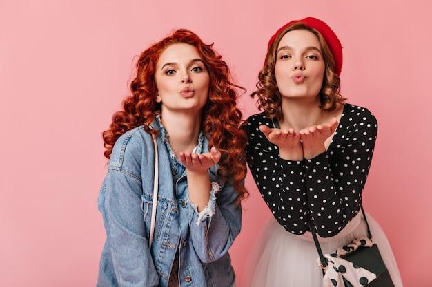 Вид спереди очаровательных дам, посылающих воздушные поцелуи. студия выстрел красивых женщин, выражающих любовь на розовом фоне.