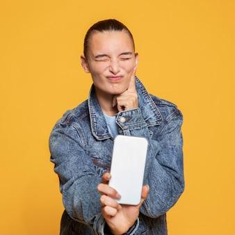 Вид спереди дерзкой женщины, держащей смартфон
