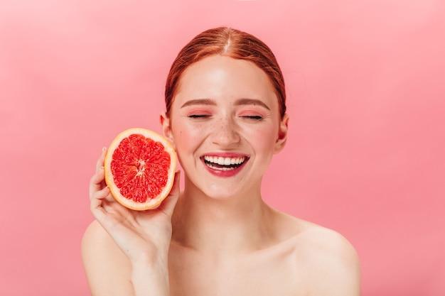 新鮮なグレープフルーツと陽気なヌードの女の子の正面図。柑橘系の熱狂的な笑顔の生姜の女性のスタジオショット。