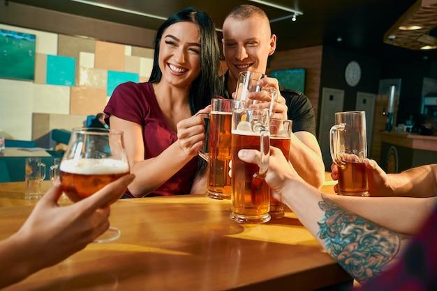 바에서 테이블에 앉아 맥주를 마시는 동안 친구들과 웃고 쾌활한 쌍의 전면 뷰. 술집에서 회사와 주말에 휴식하는 젊은 사람들. 자유 시간과 행복의 개념.