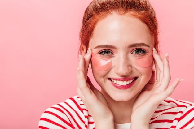 눈 패치 쾌활 한 예쁜 여자의 전면 모습. 스킨 케어 치료를 하 고 카메라를보고 행복 생강 소녀.