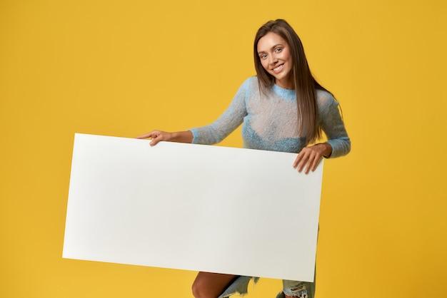 メディアバナーのプラカードを模擬した白を保持している陽気な若い女性の正面図。プリティレディーランド笑顔。黄色の壁に分離されました。創造性とデザインのコンセプト。