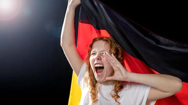 Вид спереди ликующей женщины, держащей немецкий флаг