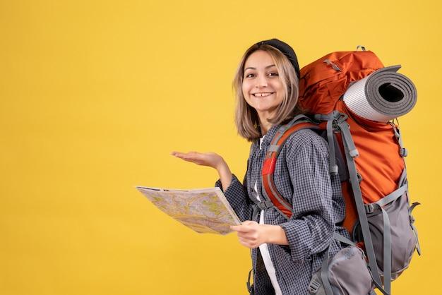 地図を保持しているバックパックと陽気な旅行者の女性の正面図