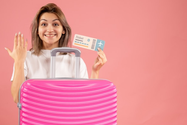 Вид спереди веселой молодой девушки с розовым чемоданом, держащей билет