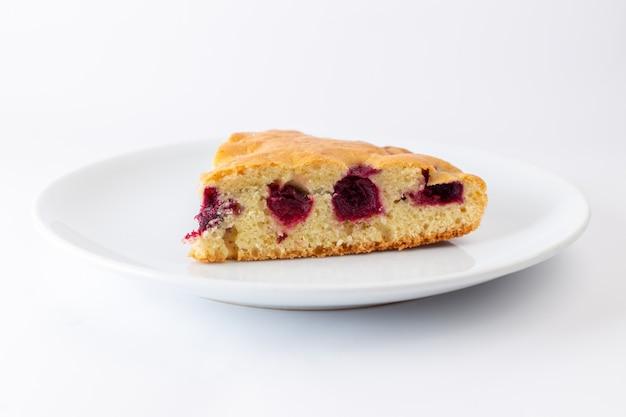 白い表面に白いプレート内の桜のケーキのスライスの正面図