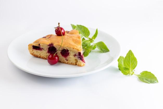 Вид спереди кусочек вишневого торта внутри белой тарелке с зелеными листьями деревьев на белой поверхности