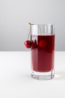 白い表面に長いガラスの中のチェリージュースの正面図