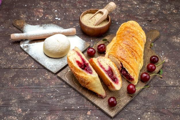 茶色の木製の机の上の新鮮でサワーチェリーとおいしい、甘いチェリーペストリーの正面図