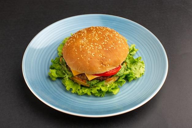 어두운 책상에 접시 안에 그린 샐러드와 야채와 치킨 샌드위치의 전면보기