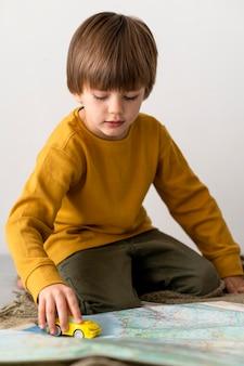 Вид спереди ребенка, играющего с игрушечной машинкой на карте