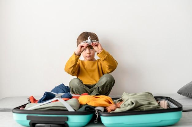 Вид спереди ребенка, сидящего рядом с багажом дома и держащего фигурку самолета