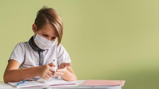 Вид спереди ребенка с медицинской маской, дезинфицирующей руки в классе с копией пространства