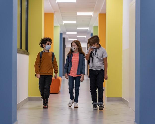 Вид спереди детей в школьном коридоре с медицинскими масками