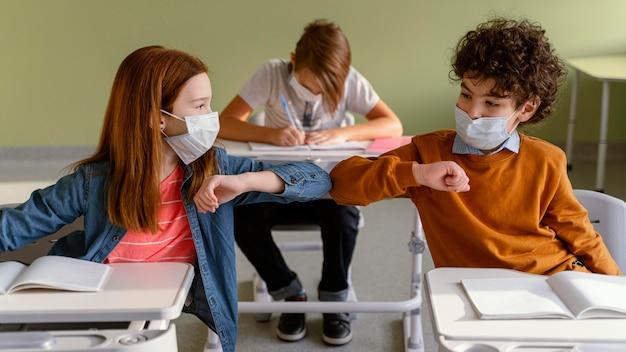 クラスで肘の敬礼をしている医療マスクを持つ子供の正面図