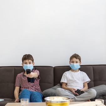 Вид спереди детей с медицинскими масками, смотрящими телевизор