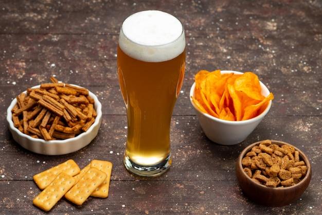 Вид спереди чипсов и чипсов вместе с пивом на коричневой деревянной