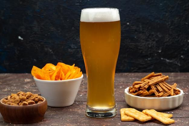 Вид спереди чипсов с крекерами вместе с пивом на темной поверхности