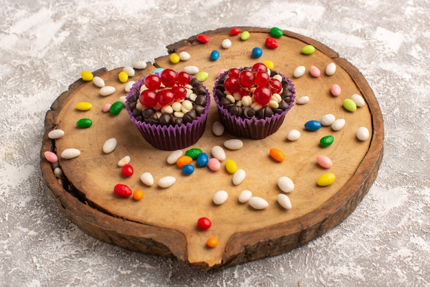 Вид спереди шоколадных пирожных с конфетами на деревянной доске