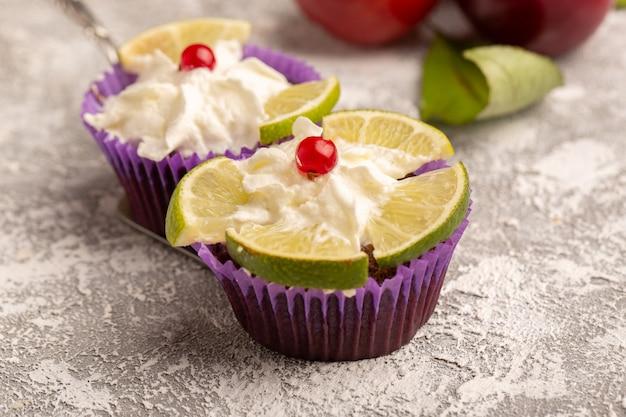 プラムと一緒にクリームとレモンのスライスとチョコレートブラウニーの正面図