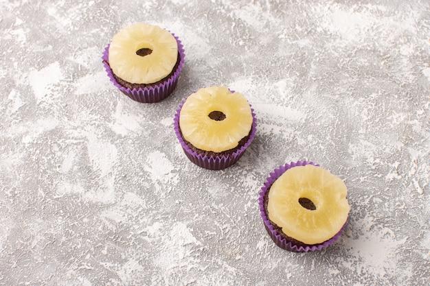Вид спереди шоколадных пирожных с ананасовыми кольцами сверху и на светлой поверхности
