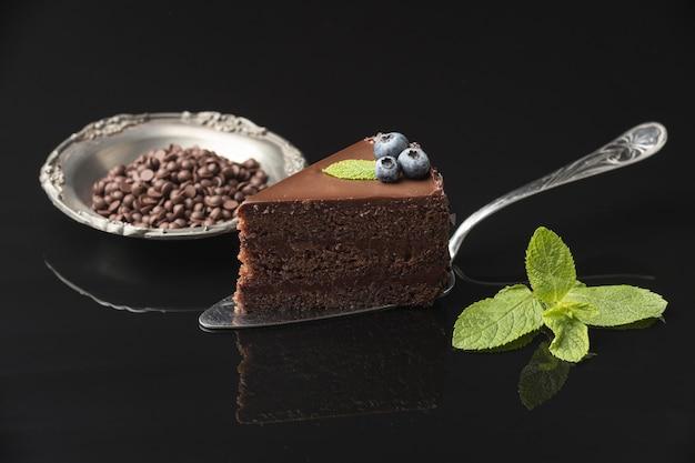 Вид спереди кусочка шоколадного торта на лопатке с мятой