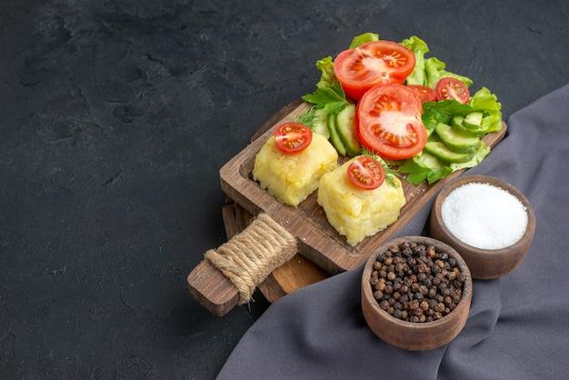 まな板の上に刻んだ新鮮な野菜のチーズと黒い表面に濃い色のタオルにスパイスを置いた正面図