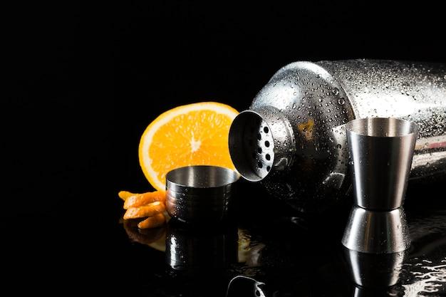 Вид спереди коктейльный шейкер с апельсином и рюмкой