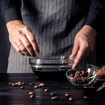 木製のテーブルの上のボウルにコーヒーの正面図