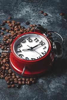 暗い表面に時計が付いているコーヒーの種の正面図