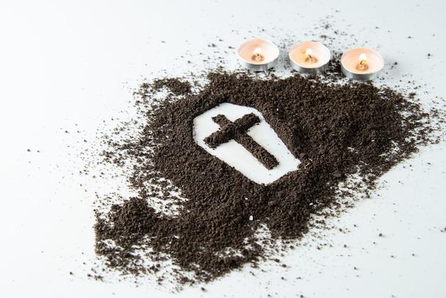 Вид спереди формы гроба с коричневой почвой и белой поверхностью свечей