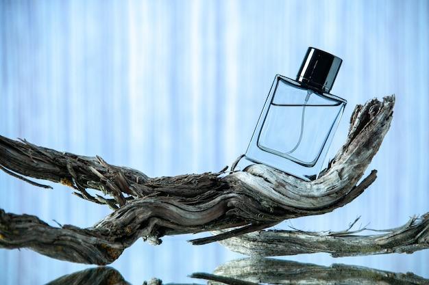 밝은 파란색 배경에 썩은 나뭇가지에 있는 향수 병의 전면 보기