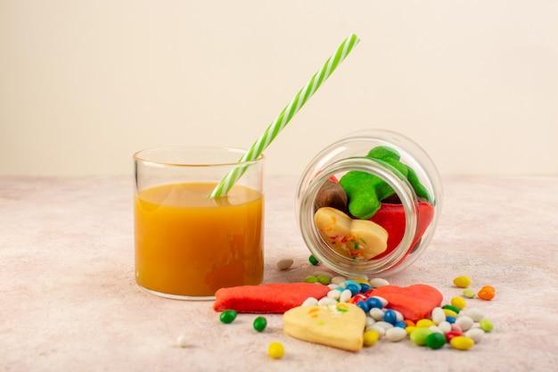 Вид спереди красочных вкусных печений различных форм внутри банка с конфетами и свежим персиковым соком