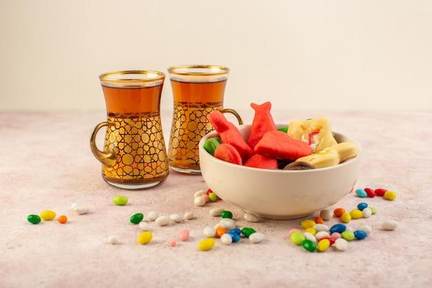 Вид спереди красочные вкусные печенья разные сформированные внутри пластины с конфетами и чашками чая