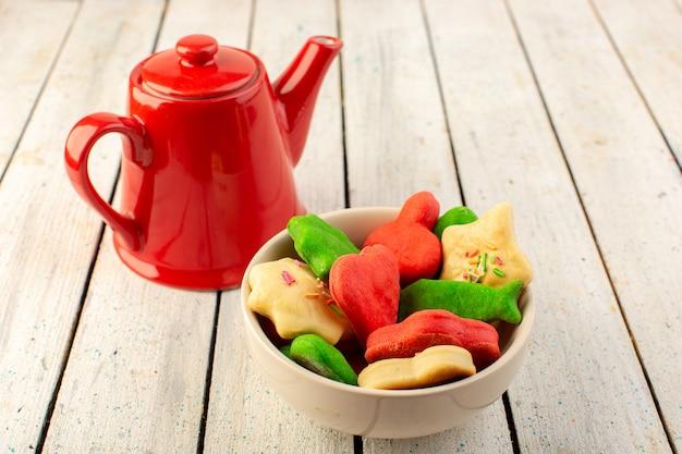 灰色の表面に赤いやかんでプレート内に形成された異なるカラフルなおいしいクッキーの正面図