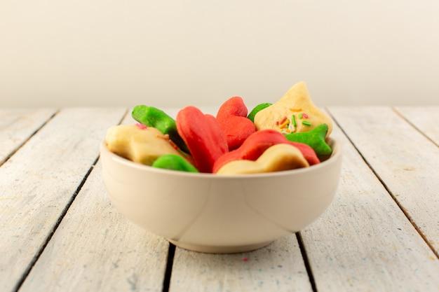 Вид спереди красочные вкусные печенья разные сформированные внутри пластины