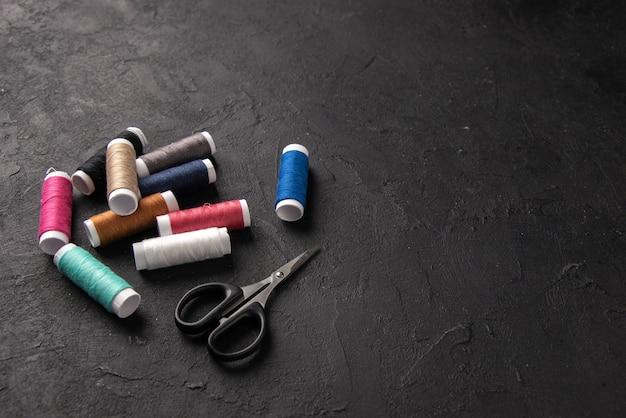 暗い机の上のカラフルな糸の正面図は戦争の邪悪な縫製死の葬式を縫う